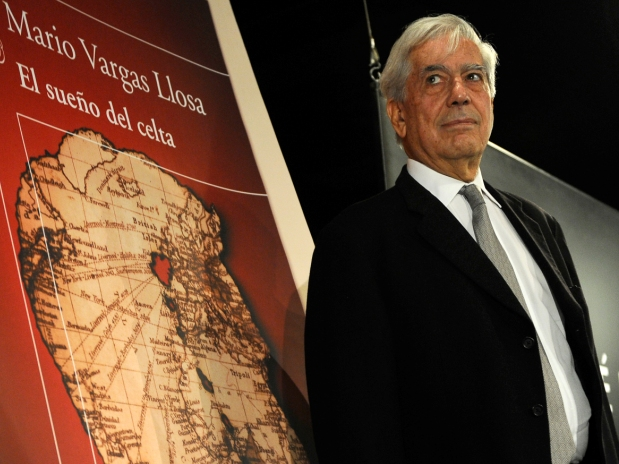 "Peruvian novelist Mario Vargas Llosa, winner of this year's Nobel Prize for literature, poses in front of a poster depicting his book "" El sueno del Celta"" (The dream of the Celt) during its presentation on November 3, 2010, in Madrid.     AFP PHOTO/ PIERRE-PHILIPPE MARCOU"